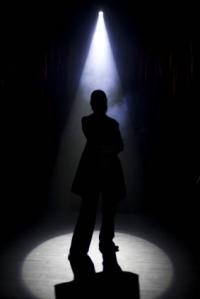 A silhouette of a person under an entertaiment light.